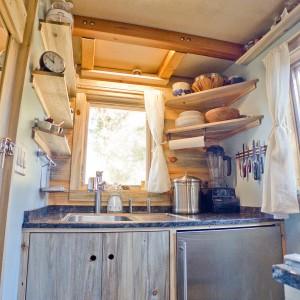 Udało się w niej jednak wygospodarować miejsce na wszystkie niezbędne elementy funkcjonalnej przestrzeni przygotowywania posiłków. Po jednej stronie pomieszczenia znajduje się blat roboczy ze zlewozmywakiem przy oknie, po drugiej - płyta grzewcza. Projekt i zdjęcia: Alek Lisefski.