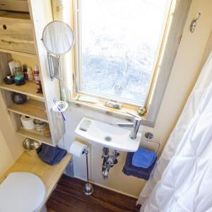 Łazienka z toaletą ma strefę prysznica po jednej stronie, umywalkę przy oknie, w centralnym miejscu pomieszczenia oraz wc z praktycznymi półkami, wkomponowanymi w zabudowę. Obecność okna zapobiega wrażeniu ciasnoty. Projekt i zdjęcia: Alek Lisefski.