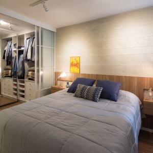Sypialnię połączono z obszerną garderobą, do której prowadzą przesuwne drzwi z mlecznego, matowego szkła. Taka aranżacja pozwala zachować porządek w pomieszczeniu, a przy tym go nie przytłacza. Projekt: Semerene Arquitetura Interior. Fot. Joana França.