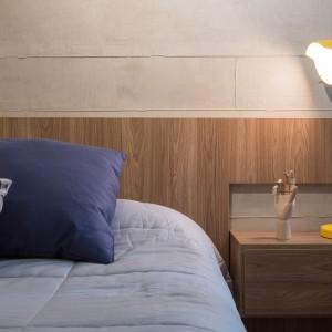 W całym mieszkaniu postawiono na podobną paletę kolorów. Przestrzeń sypialni ożywiono żółtymi elementami, podobnie jak strefę dzienną. Tutaj barwnym detalem jest industrialna lampka nocna. Projekt: Semerene Arquitetura Interior. Fot. Joana França.