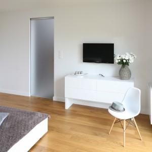 Białe, nowoczesne meble pięknie prezentują się w duecie z jasnym drewnem. Szklane drzwi skrywają natomiast komfortową kę. Projekt: Małgorzata Galewska. Fot. Bartosz Jarosz.