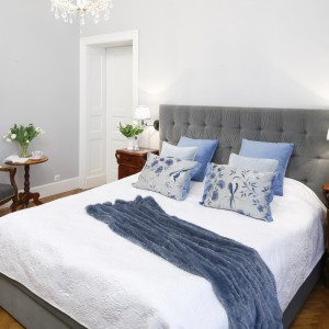 Szykowna sypialnia urządzona z wykorzystaniem klasycznych, drewnianych mebli oraz eleganckiego łóżka tapicerowanego szarym aksamitem. Lekkości dodają aranżacji liliowe dekoracje. Projekt: Iwona Kurkowska. Fot. Bartosz Jarosz.