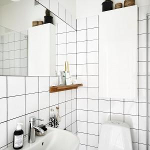 Łazienka to proste formy i wszechobecna biel. Dzięki temu ma bardzo współczesny charakter i jednocześnie nie przeraża ciasnotą. Elementem delikatnie ocieplającym wizualnie tę monochromatyczną przestrzeń jest drewniana półeczka na akcesoria łazienkowe. Fot. Stadshem.