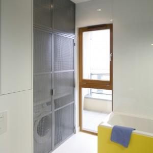 W nowocześnie urządzonej łazience zdecydowano się na ażurowe fronty szafy za którymi ukryto pralkę i wiele miejsca na przechowywanie. Projekt: Monika i Adam Bronikowski. Fot. Bartosz Jarosz.