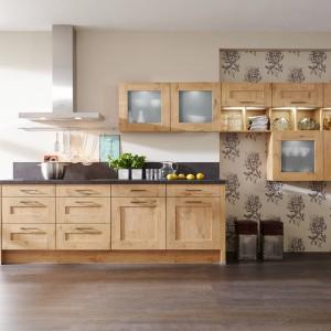 Delikatnie klasycyzujące meble w ciepłym kolorze drewna. Frezowane fronty dolnej zabudowy idealnie harmonizują z górnymi szafkami. Te jednak, oprócz inspiracji tradycyjną stylistyką, wprowadzają również element asymetrii do przestrzeni kuchni. Choć poszczególne przeszklone szafki są bliskie kształtem sześcianowi, dwie z nich zamontowano wyżej, dwie niżej, a łączy je pas trzech kolejnych szafek, które zostały  podzielone na pół, przy czym ich dolne połowy zostały zagospodarowane na otwarte, drobne półki. Całość wygląda wdzięcznie i fantazyjnie. Fot. Impuls, program IP 6120.