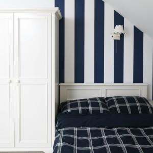 Niewielki metraż sypialni dodatkowo ograniczają skosy. Aby wnętrze wydawało się wyższe, ścianę za łóżkiem ozdobiono tapetą w granatowo-białe pasy. Projekt: Katarzyna Mikulska-Sękalska. Fot. Bartosz Jarosz.