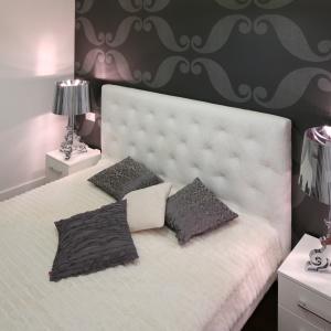 Białe tapicerowane łóżko idealnie komponuje się z eleganckimi lampkami oraz dekoracyjną tapetą. Wąskie stoliki nocne idealnie uzupełniają stylistykę wnętrza.   Projekt: Katarzyna Mikulska-Sękalska. Fot. Bartosz Jarosz.
