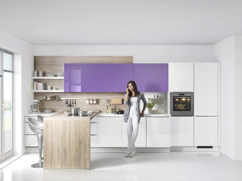 Zestawiając ze sobą zabudowę w różnych kolorach można w prosty sposób nadać kuchni bardziej fantazyjny charakter. Biała dolna zabudowa oraz wysokie słupki na sprzęt AGD ciekawie ożywiono fioletowymi szafkami górnymi. Dodatkowym elementem nadającym całej aranżacji lekkość są otwarte półki, niejako wyrastające z fiołkowych frontów. Całość ociepla drewniany panel w tle. Fot. Nolte Kuechen, model Viola Hochglanz i Weisz Hochglanz.