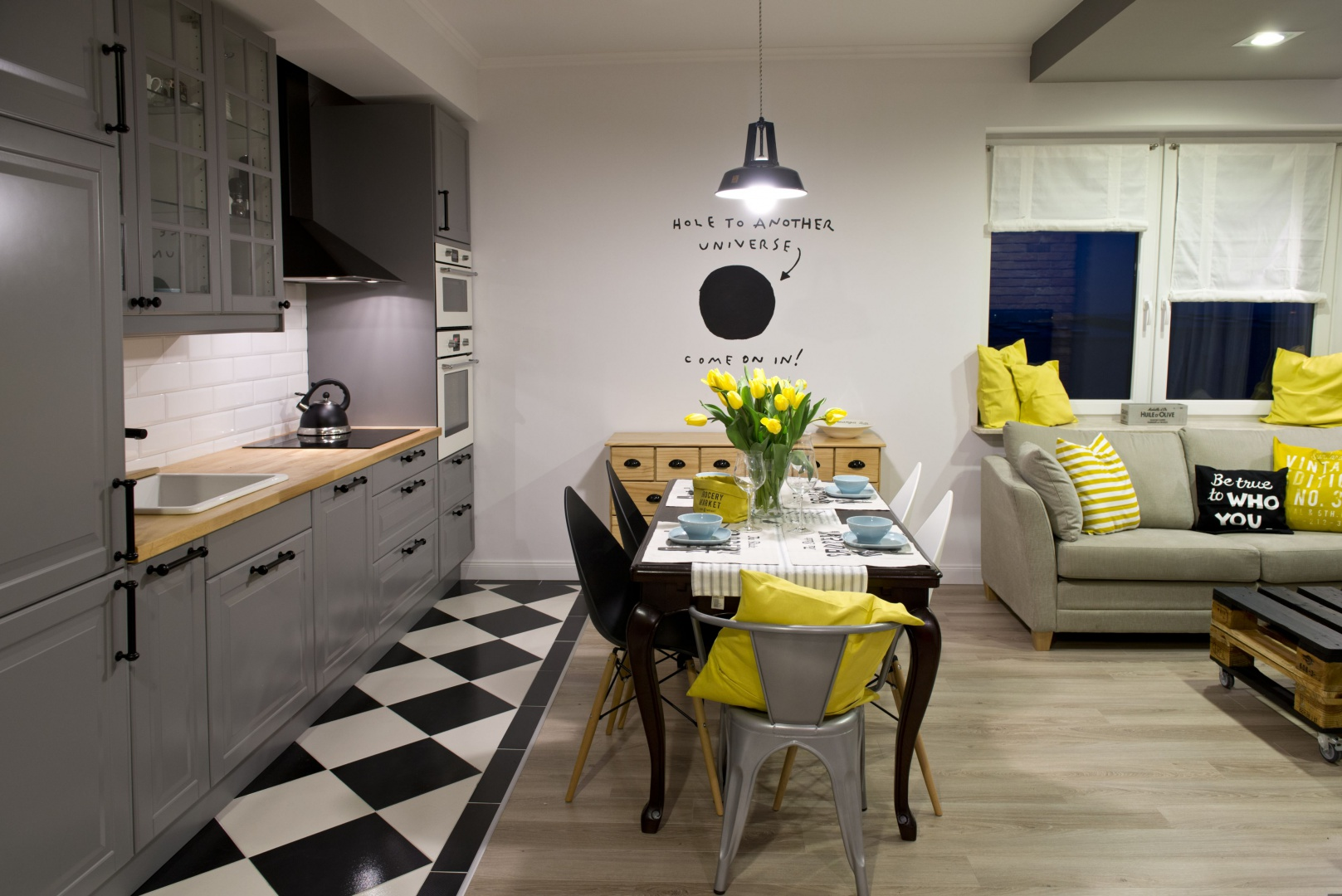 Aneks kuchenny od salonu oddziela stół jadalniany oraz towarzysząca mu komoda. Czarny stół wspiera się na stylizowanych nogach, a towarzyszące mu czarne i białe krzesła wyraźnie nawiązują do eamesowskich klasyków. Z industrialną lampą nad stołem harmonizuje szare krzesło, pomalowane metaliczną farbą, która kolorem koresponduje również z zabudową kuchenną. Projekt: SHOKO.design. Fot. Małgorzata Opala.