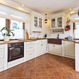 Meble kuchenne w kolorze złamanej bieli ocieplają elementy w kolorze drewna: blat i stolarka okienna. Duże okna pięknie doświetlają pomieszczenie, pozostawiając miejsce na dwie szafki wiszące z przeszklonymi drzwiczkami. Wzrok przyciąga niesamowity zlewozmywak, nakładany na blat. Wykonany z metalu, z kutymi zdobieniami stanowi najefektowniejszy element aranżacyjny tej kuchni. Projekt i zdjęcia: Kamila Paszkiewicz.