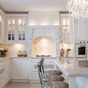 W tej pięknej kuchni, fronty w kolorze ecru połączono z blatami w zbliżonym kolorze. Górne szafki zdobią liczne przeszklenia o różnym kształcie, przybrane dekoracyjnymi szprosami, efektownie podświetlone od środka. Z klasyczną zabudową harmonizuje piekarnik w stylu retro w kremowym kolorze. Projekt: Małgorzata Błaszczak. Fot. Pracownia Mebli Vigo.