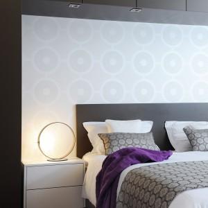 Zabudowa z matowymi, antracytowymi frontami, która pokrywa część ściany nad łóżkiem koresponduje z meblami w kuchni. Projekt: GAO Arhitekti. Fot. Mateja Jordovič Potočnik.