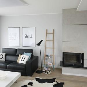 Ścianę z kominkiem w salonie zdobi beton architektoniczny, który wyeksponowano w ten sposób, by przypominał tradycyjne betonowe bloczki. Projekt: Beata Kruszyńska. Fot. Bartosz Jarosz.