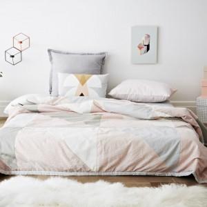 Pomysł na sypialnię dla minimalistów. Niewielką ilość wyposażenia: niskie łóżko i stolik nocny, rekompensuje obecność pastelowych kolorów w postaci pościeli. Fot. Norsu Interiors.
