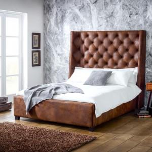 Łóżko z wysokim, pikowanym wezgłowiem sprawia, że nowoczesna sypialnia zyskuje szykowny wygląd. Urodę meble eksponuje szara ściana o fakturze kamienia, równoważąca ciepłe elementy wyposażenia. Fot. Living It Up.