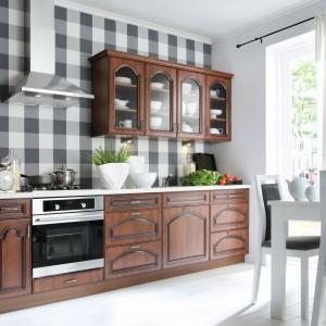 Klasyczne meble w ciepłym kolorze drewna wprowadzają przytulną, domową atmosferę do przestrzeni kuchni. W tej aranżacji zdecydowano się na rozwiązanie, które wyeksponuje wizualnie aneks kuchenny, poprzez jego mocną, kontrastującą z otaczającymi go jasnymi kolorami. Fot. Black Red White, model Kapelo.