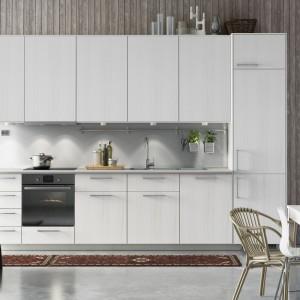 Eleganckie meble z frontami w kolorze bielonego drewna pięknie prezentują się w otwartej przestrzeni dziennej, urządzonej w popielatych kolorach. Fot. IKEA.
