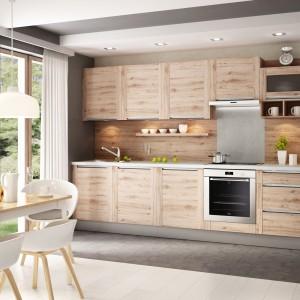 Aneks kuchenny nie może być urządzany w oderwaniu od przestrzeni dziennej, z którą powinien korespondować, harmonizując, bądź kontrastując w elegancki sposób. W tej aranżacji fronty mebli kuchennych w beżowym odcieniu drewna idealnie współgrają z jasnym stołem jadalnianym. Zabudowa kuchenna wypełnia niewielką wnękę, dzięki czemu oświetlenie nad blatem można było zainstalować w suficie podwieszanym, stanowiącym ramę dla mebli. Fot. KAM Kuchnie, model Olivia Soft.
