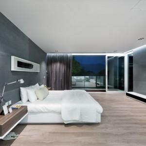 Duża, przestronna sypialnia pani i pana domu zachwyca ilością przestrzeni i oszczędnym wystrojem. Punktem centralnym jest duże, eleganckie, białe łoże. Projekt i zdjęcia: Millimeter Interior Design.