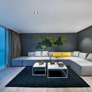 Dominujące we wnętrzu szarości przełamują żywsze detale w postaci żółtych poduszek dekoracyjnych i dekoracji na ścianie. Projekt i zdjęcia: Millimeter Interior Design.