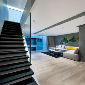 Poszczególne piętra skomunikowano nowoczesnymi schodami, które otwierają się na poszczególne kondygnacje, chowając delikatnie jedynie za niewielką, szklaną ścianką. Projekt i zdjęcia: Millimeter Interior Design.