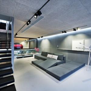 We wnętrzu dominują modne szarości i efekt betonu, budujący delikatnie industrialny klimat w całym domu. Z urbanistyczną stylistyką harmonizuje poprowadzone pod sufitem na czarnych listwach, techniczne oświetlenie. Projekt i zdjęcia: Millimeter Interior Design.