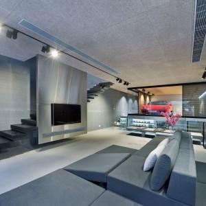 Wspornikowe schody chowają się za zabudową, na której zawisł telewizor. Stalowy panel połyskuje i przyciąga wzrok, konkurując z przeszklonym garażem. Projekt i zdjęcia: Millimeter Interior Design.