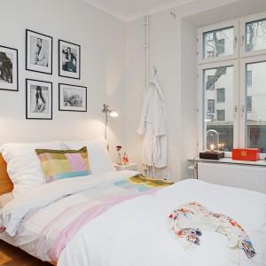 Dominującym kolorem w tej sypialni jest biel, która optycznie powiększa wnętrza i sprawia, że jest jasne i pełne światła. Aranżację ociepla piękny kolory drewna zastosowany na podłodze i na ramie łóżka. Oryginalnym akcentem są z kolei czarno-białe zdjęcia. ot. Alvhem Mäkleri.