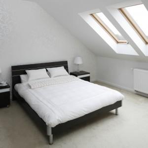 Białą sypialnię dodatkowo rozjaśniają promienie słoneczne wpadające przez okna dachowe. Pięknie eksponują one wzór na perłowej tapecie, zdobiącej ścianę za łóżkiem. Projekt: Magdalena Biały. Fot. Bartosz Jarosz.