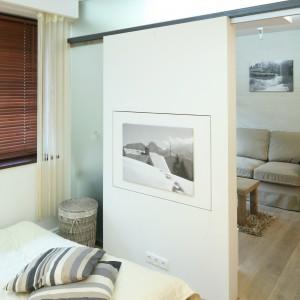 Sypialnię od salonu oddziela biała ścianka oraz wysuwane drzwi ze szkła. Oba wnętrza łączy podłoga z jasnego drewna, harmonizująca z dominującą bielą. Projekt: Łukasz Sabat. Fot. Bartosz Jarosz.