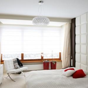 W przestronnej sypialni biel harmonijnie współgra z ciepłym, jasnym beżem. Pikowana ściana za łóżkiem oraz dekoracyjna lampa sufitowa sprawiają, że aranżacja zyskuje glamourowy szyk. Projekt: Katarzyna Mikulska-Sękalska. Fot. Bartosz Jarosz.