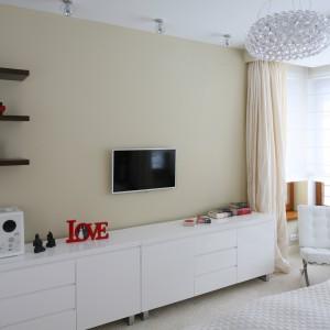 Funkcję przechowywania pełni niska szafka na całą szerokość ściany. Charakteru dodają jej czerwone detale. Projekt: Katarzyna Mikulska-Sękalska. Fot. Bartosz Jarosz.