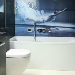 W czarno-białej łazience, nad wanną umieszczono fototapetę, która wprowadza do wnętrza odrobinę koloru. Projekt: Monika i Adam Bronikowscy. Fot. Bartosz Jarosz.