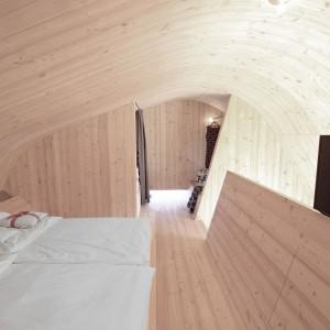 Goście mają do dyspozycji wszystkie wygody mieszkania w hotelu. W sypialni na drewnianym wzniesieniu znalazło się nawet miejsce na sporych rozmiarów telewizor. Projekt: Architekturbüro Jungmann&Aberjung Design Agency. Fot. DI Lukas Jungmann/Familie Pitterl.
