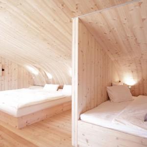 Usytuowana na antresoli sypialnia mieści dwa łóżka: jedno duże, drugie mniejsze, schowane za niepełną ścianką. Projekt: Architekturbüro Jungmann&Aberjung Design Agency. Fot. DI Lukas Jungmann/Familie Pitterl.