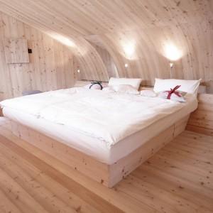 Wzdłuż sypialni, pod jej ścianą, poprowadzono długą szafkę, która funkcjonuje również jako wezgłowie dwuosobowego łoża. Zamontowano na niej lampki nocne. Projekt: Architekturbüro Jungmann&Aberjung Design Agency. Fot. DI Lukas Jungmann/Familie Pitterl.