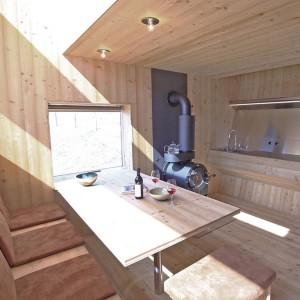 Zimą goście mogą się ogrzać kominkiem, który usytuowano na granicy jadalni i kuchni. Projekt: Architekturbüro Jungmann&Aberjung Design Agency. Fot. DI Lukas Jungmann/Familie Pitterl.