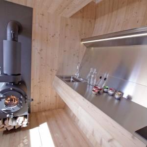 Aneks kuchenny został zabezpieczony stalowymi panelami. W połączeniu z okalającym je drewnem, połyskujące, metaliczne powierzchnie prezentują się bardzo futurystycznie. Rzeczywiście można mieć wrażenie, że jest się we wnętrzu statku kosmicznego! Projekt: Architekturbüro Jungmann&Aberjung Design Agency. Fot. DI Lukas Jungmann/Familie Pitterl.