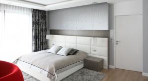 W nowoczesnej, przestronnej sypialni króluje srebrzysta szarość. Wyjątek stanowi czerwony fotel, wyznaczający kobiecy zakątek.