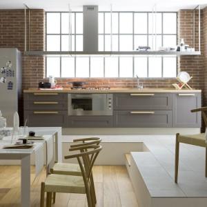 Aranżacja w delikatnie loftowej stylistyce. Szarą zabudowę kuchenną i liczne stalowe elementy połączono z czerwoną cegłą na ścianie, której barwa pięknie eksponuje szare meble. Fot. Veneta Cucine, model California 7.