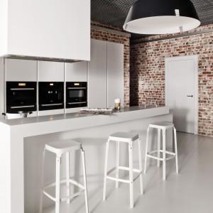 Biała, minimalistyczna kuchnia z wysoką zabudową i długą wyspą ma mocny, czerwony akcent w postaci cegły na ścianie. Materiał harmonizuje z czarnymi loftowymi lampami. Fot. Zajc Kuchnie.