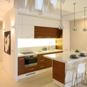 Aneks kuchenny z wyspą, pełniącą funkcję baru został urządzony w dwóch kolorach: bieli, harmonizującej ze ścianą, zamykającą kuchnię od strony przedpokoju oraz w ciepłym kolorze drewna. Projekt: Małgorzata Galewska. Fot. Bartosz Jarosz.