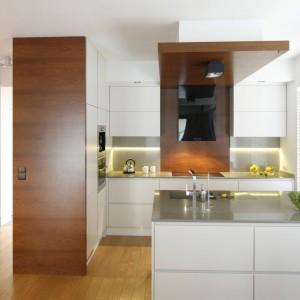 Nowoczesna kuchnia z wyspą zachwyca oszczędną, geometryczną aranżacją. Zabudowę i ścianę nad blatem dzieli panel, wykończony fornirem w ciepłym, głębokim kolorze drewna. Element przechodzi w płynnie w podwieszany sufit, stanowiąc nietuzinkowe rozwiązanie aranżacyjne. Ścianę nad blatem dodatkowo zdobi szare szkło, idealnie korespondujące z szarą powierzchnią roboczą. Projekt: Kamila Paszkiewicz. Fot. Bartosz Jarosz.