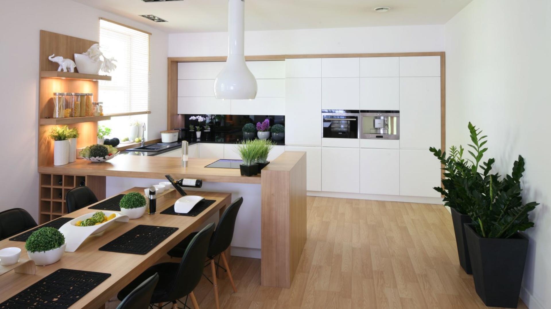 Nowoczesna kuchnia z białymi frontami wykończonymi w macie. Zabudowa kuchenna na jedną ścianę przyciąga wzrok, dominując nad całością aranżacji. Oprawiona w okalającą ją drewnianą ramę prezentuje się nadzwyczaj efektownie. Towarzyszy jej półwysep z drewnianym blatem, przy którym ustawiono długi, drewniany stół. Projekt: Małgorzata Błaszczak. Fot. Bartosz Jarosz.