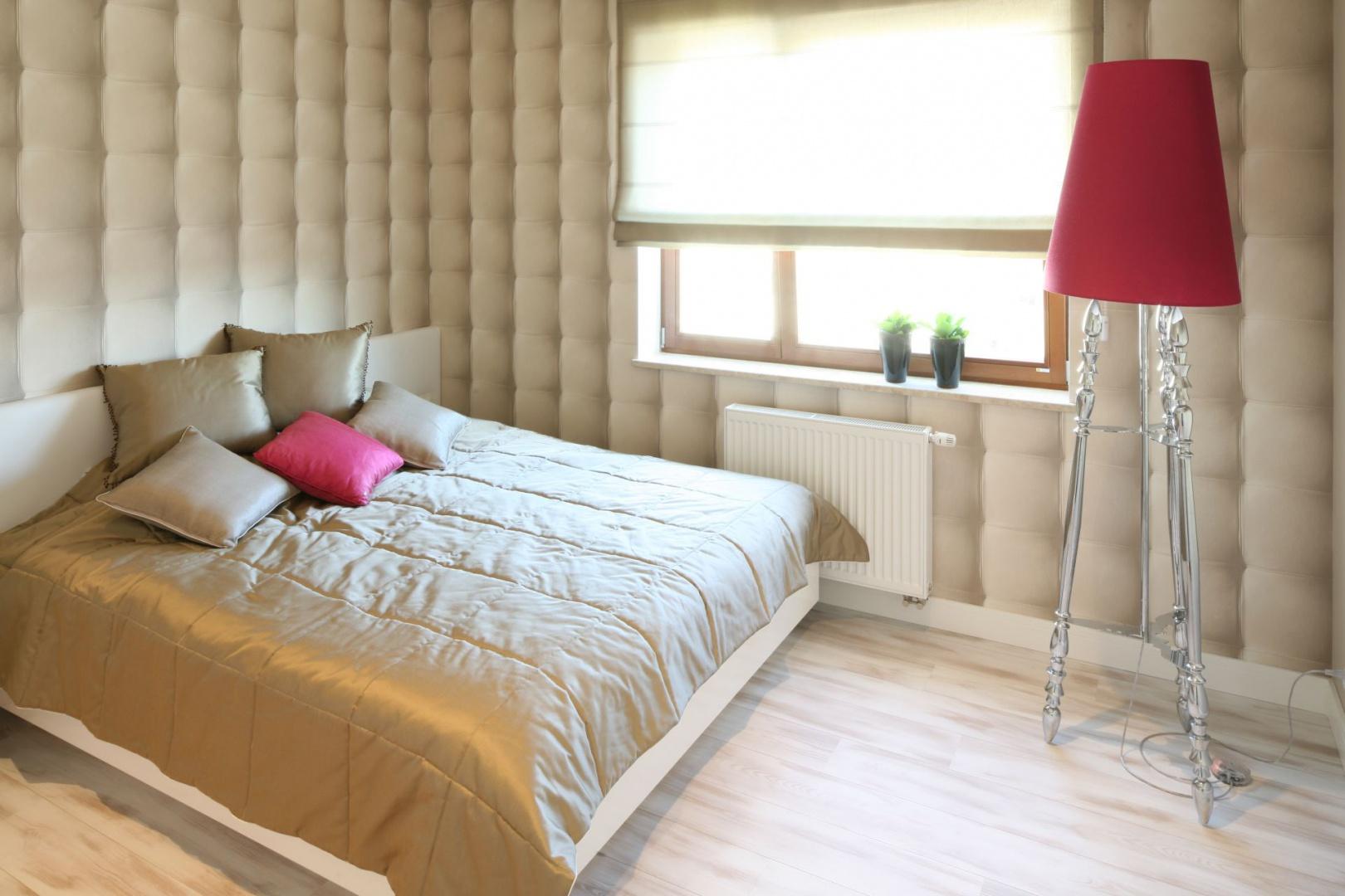 Tapeta imitująca charakterystyczne, pikowane przeszycia sprawia, że sypialnia wygląda przytulnie i niezwykle efektownie. W tak dekoracyjnej aranżacji znakomicie prezentuje się prosta dekoracja okna w formie rolety. Projekt: Karolina Łuczyńska. Fot. Bartosz Jarosz.