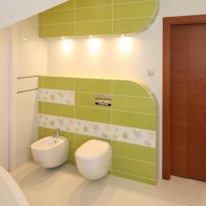 W tej kolorowej łazience dominują zaokrąglone kształty, których nie mogło zabraknąć na ścianie z miską ustępową i bidetem. Wnękę nad zabudową oświetlono delikatnym, dekoracyjnym światłem. Projekt: Magdalena Bonin-Jarkiewicz. Fot. Bartosz Jarosz