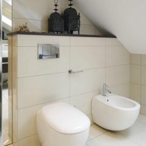 W łazience urządzonej na poddaszu zdecydowano się na zaznaczenie stelaża półką, która kolorystycznie kontrastuje z jasnymi płytkami. Projekt: Magdalena Wielgus-Biały. Fot. Bartosz Jarosz.