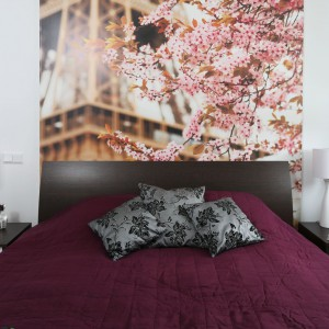 Piękną, elegancką sypialnię wypełnia słodki zapach kwitnących jabłoni. Wszystko za sprawą romantycznej fototapety naklejonej na ścianie za łóżkiem. Projekt: Anna Maria Sokołowska. Fot. Bartosz Jarosz.