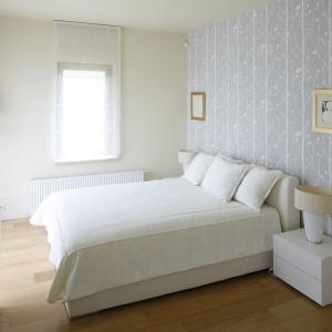 Białe łóżko usytuowane centralnie na największej ścianie w sypialni, która jednocześnie stanowi najbardziej widoczny element w pokoju, ponieważ została udekorowana tapetą. Projekt: Małgorzata Borzyszkowska. Fot. Bartosz Jarosz.