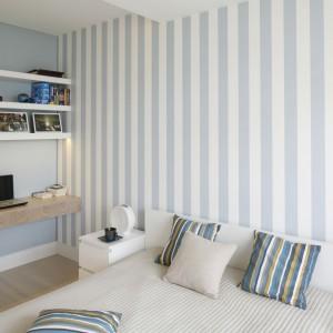 Wąskie, pionowe pasy to sprawdzony sposób na to, aby optycznie powiększyć sypialnię. Taki rodzaj tapety warto zastosować w delikatnym, pastelowym kolorze, ponieważ doskonale rozjaśni on pomieszczenie. Projekt: Agnieszka Zaremba, Magdalena Kostrzewa-Świątek. Fot. Bartosz Jarosz.